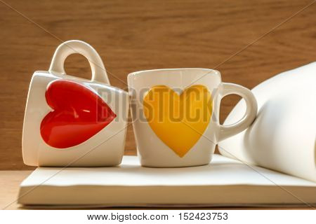Two cups on book with red and yellow heart-shaped on wooden tablefocused on cups