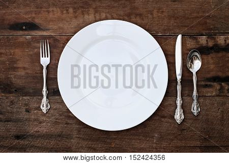 Place setting of a dining set of an empty plate with spoon fork and knife over a rustic old wooden background. Image shot from overhead.