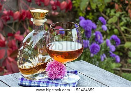 Bottle and a snifter of brandy with flower on the old table in autumn garden's