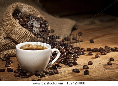 Coffee cup and sack with coffee beans on a wooden background.