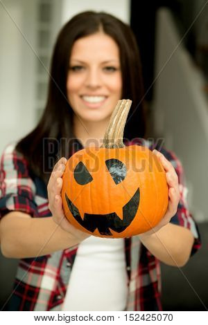 Attractive brunette woman at home with a halloween pumpkin. Selective focus