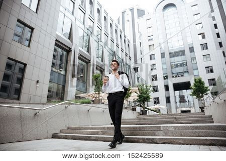 Happy young businessman walking and drinking coffee near business center