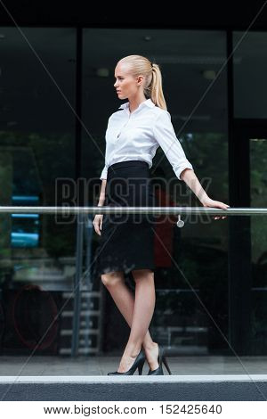 Full length portrait of a confident businesswoman standing outdoors and leaning on the glass railing