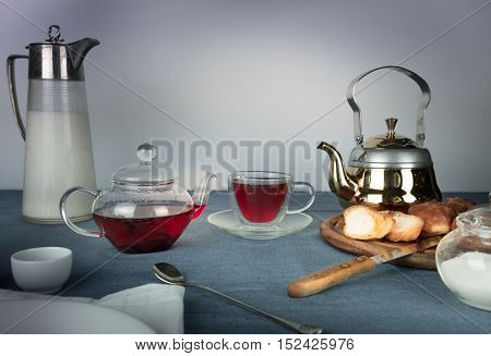 jug of milk, hibiscus tea, buns on a blue tablecloth