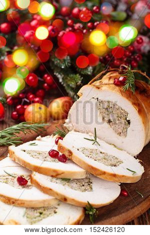 Stuffed turkey breast with pomegranate and rosemary on cutting board.