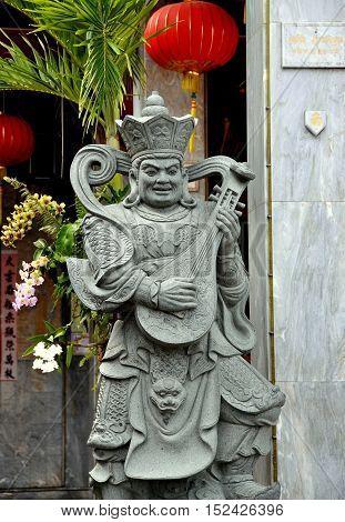 Phuket City Thailand - January 8 2011: Stone Buddha figure playing a lute at the Jut Lut / Shui Dui Dou Mu Gong Chinese Taoist temple
