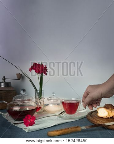 woman's hand, cup of tea on the table with tea, scones and geranium flower in a vase