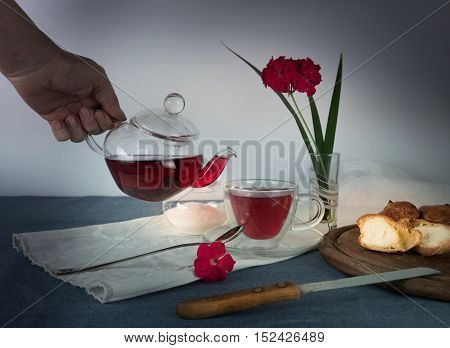 hand pouring tea from a teapot into glass cup