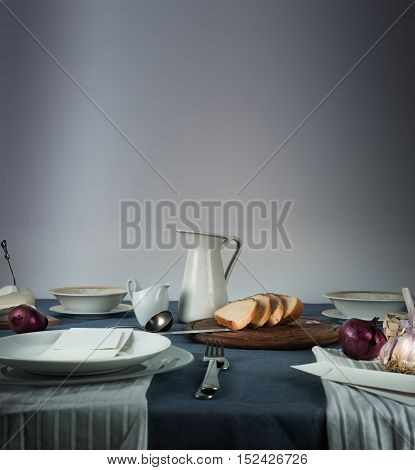 still life. jug, bread on a blue tablecloth