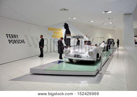 STUTTGART, GERMANY - APRIL 21, 2015. The white interior of the Porsche cars museum. Metallic retro car and visitors. Stuttgart, Germany.