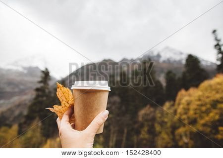 Drinking take away coffee in mountains. Fall trip. Rain weather. Freedom travel concept. Autumn weekend in forest.