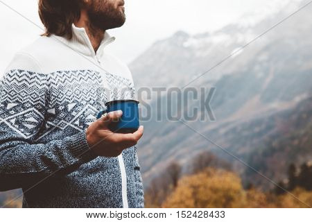 Hiker wearing sweater holding tin mug. Man drinking warm tea or coffee in the morning outdoor. Camping hiking concept. Autumn travel in mountains, cold weather. Noface photo.
