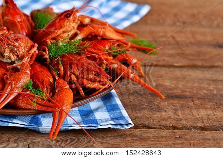 Fresh boiled crayfish with dill on a large plate on a wooden background.
