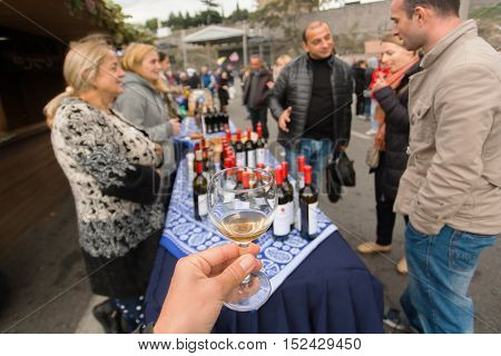 TBILISI, GEORGIA - OCT 16, 2016: People tasting wine around table with wine bottles during festival Tbilisoba on October 16, 2016. Tbilisoba is traditional festival in capital of Georgia from 1979