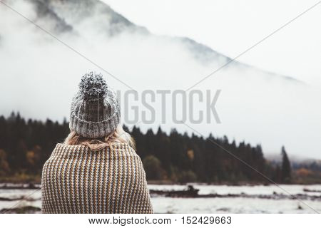 Hiker girl wrapping in warm blanket outdoor. Hiking in mountains in autumn. Bad weather with fog. Cold morning by the river.