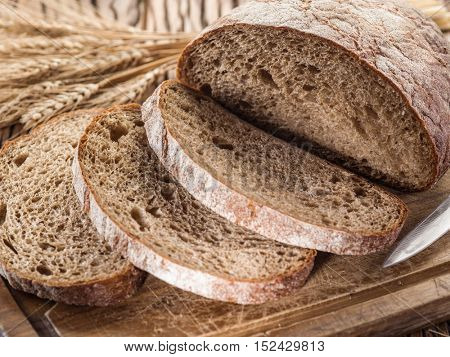 Sliced black bread on the old wooden plank. Bread background.