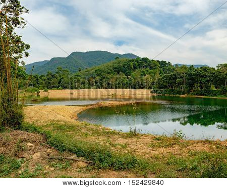 Dense tropical vegetation under the blue sky, Mu Koh Chang National Park, Chang island, Thailand. Mountains covered with various tropical trees and beautiful lake with reflection of nature in water.