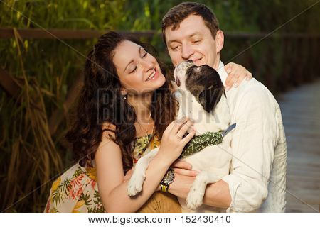 Man and woman sitting with dog looking each other