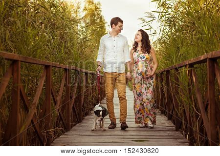 Man and pregnant woman walk with the dog