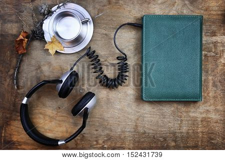 audiobook headphones and book on a wooden table