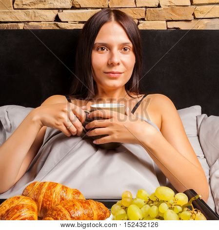Woman lying in bed and drinking morning coffee. Beautiful young brunette going to have a breakfast with a cup of coffee, fruits and croissants on a tray.