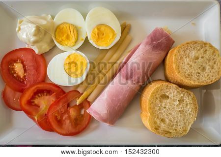half boiled eggs sliced tomatoes bread ham in a plate. French food