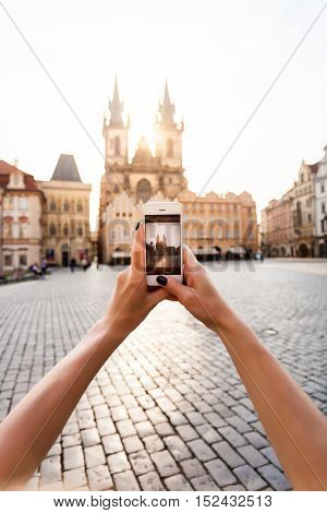 Beautiful young female traveler making photo on her mobile phone of the Church of Virgin Mary in Old Town Square in Prague. Kostel Panny Marie pred Tynem. Phone in hand closeup