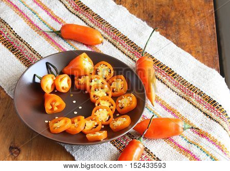 Plate of orange chili pepper rings with seeds and whole chili peppers on table with colorful place mat