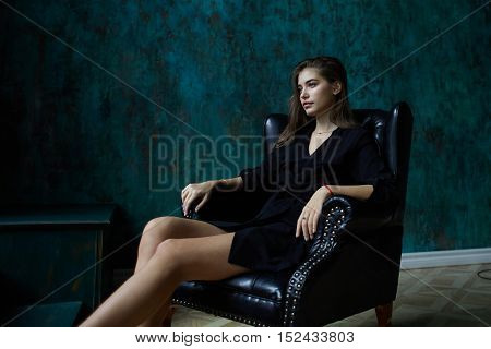 young sexy woman in black trench coat sitting in leather chair in dark classic interior