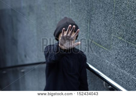 dramatic portrait of a little homeless boy dirty hand poverty city street