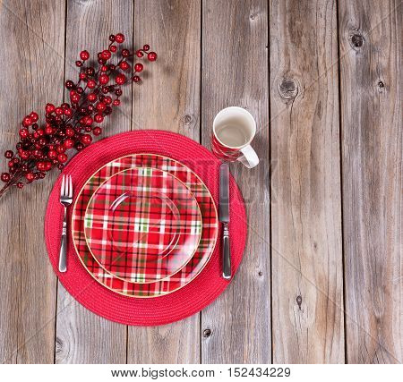 Overhead view of a festive Christmas dinner setting with red berry decorations on top of rustic wood
