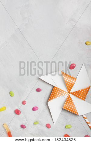 Orange party whirligig with white stars and candies on concrete background vertical orientation