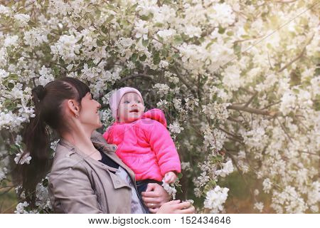 Happy beautiful girl of European appearance with her baby in the park