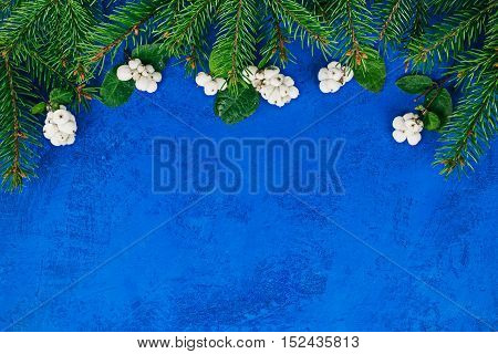 Top framework of evergreen and snowberry twigs over painted blue surface