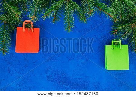 Frame of shopping bags hanging on the christmas tree twigs. Concept of christmas sale and gifts