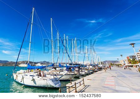 Sailing ships and yachts stand moored in the port of Volos, Greece