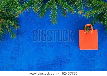 Frame of red shopping bag hanging on the christmas tree twigs. Concept of christmas sale and gifts