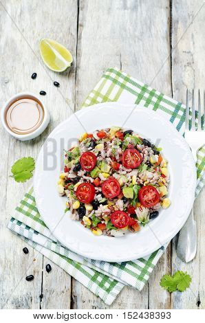 Red and white rice black beans corn avocado tomato salad. toning.