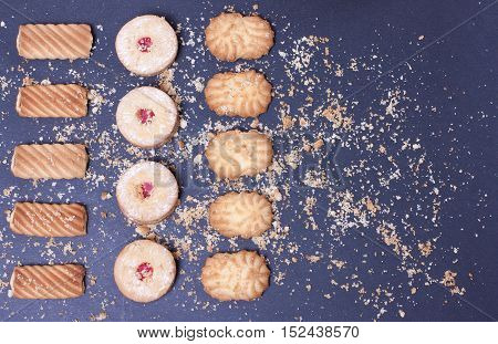 Three rows of freshly baked cookies with powdered sugar shot from above on an black baking background . Top view flat view.