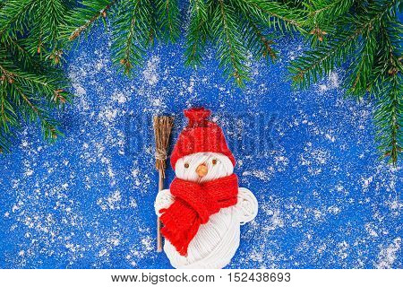 Toy handmade snowman holding broom in the framework of evergreen twigs over painted blue surface covered with snow-like powder