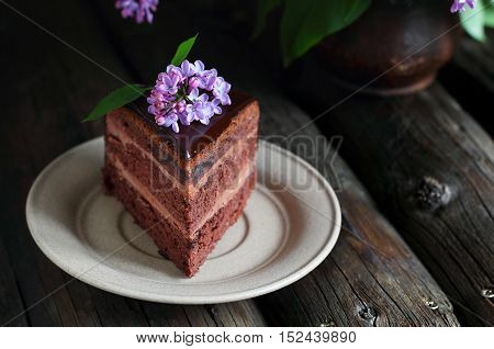 piece of homemade chocolate cake decorated with lilac on a wooden background