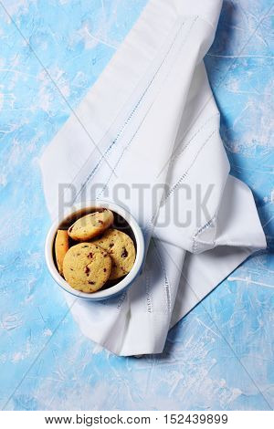homemade cookies with dried cranberries and corn flour in a blue bowl on a blue background