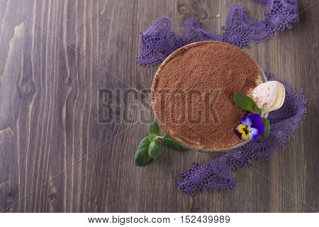 Traditional Italian Tiramisu dessert in glass on a wooden table