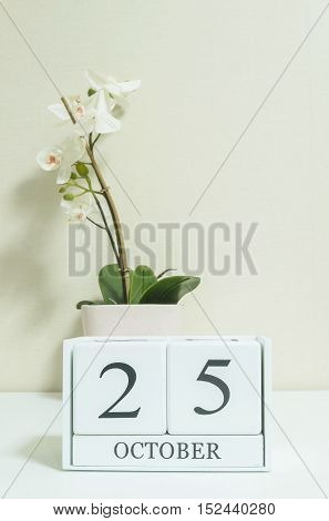 Closeup white wooden calendar with black 25 october word with white orchid flower on white wood desk and cream color wallpaper in room textured background selective focus at the calendar