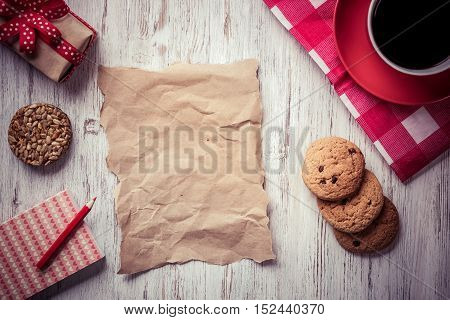 Sheet of paper coffee cup and cookies top view on wooden table