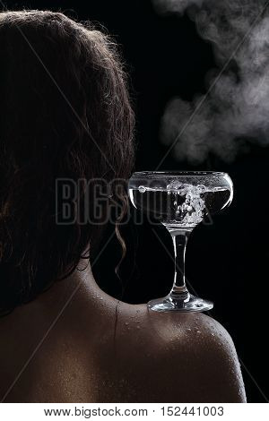 glass of boiling water on the wet shoulder of a girl natural steam over the glass (from a steam iron) on a black background