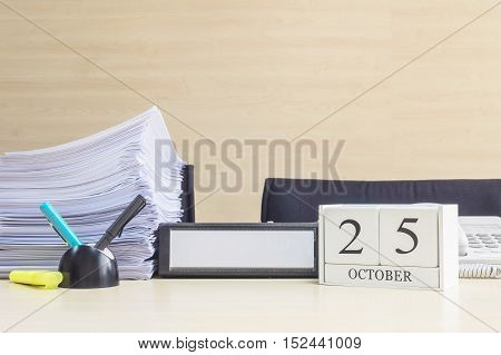 Closeup white wooden calendar with black 25 october word on blurred brown wood desk and wood wall textured background in office room view with copy space selective focus at the calendar