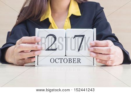Closeup white wooden calendar with black 27 october word in blurred working woman hand on wood desk in office room selective focus at the calendar