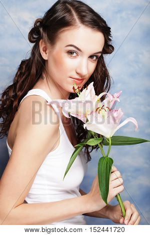 Beauty face of the young woman with pink lily isolated on white