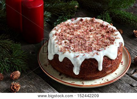 homemade cake with persimmon decorated with frosting cream cheese and sprinkled with chocolate in the New Year decorations